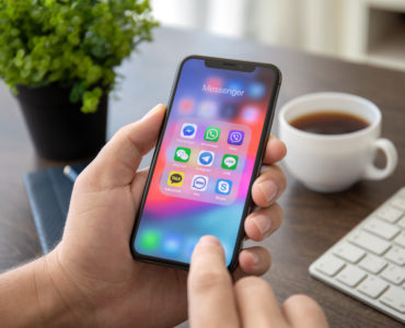 Man hand holding iPhone X with social networking Messenger