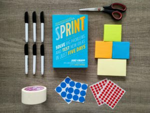 a brown table with six marker pens cellotape blue and red dot stickers scissors post it notees and the design sprint book